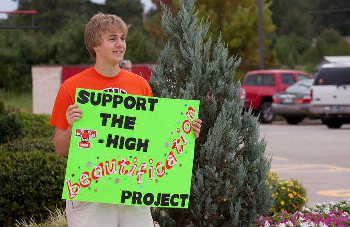 Senior Jacob Hill holds up a sign at Chicken Express to help TYTL with their fundraiser