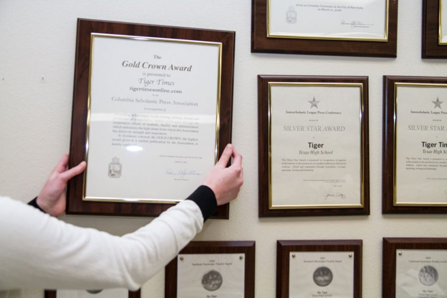 Newspaper adviser Rebbecca Potter hangs the Gold Crown award on the wall.