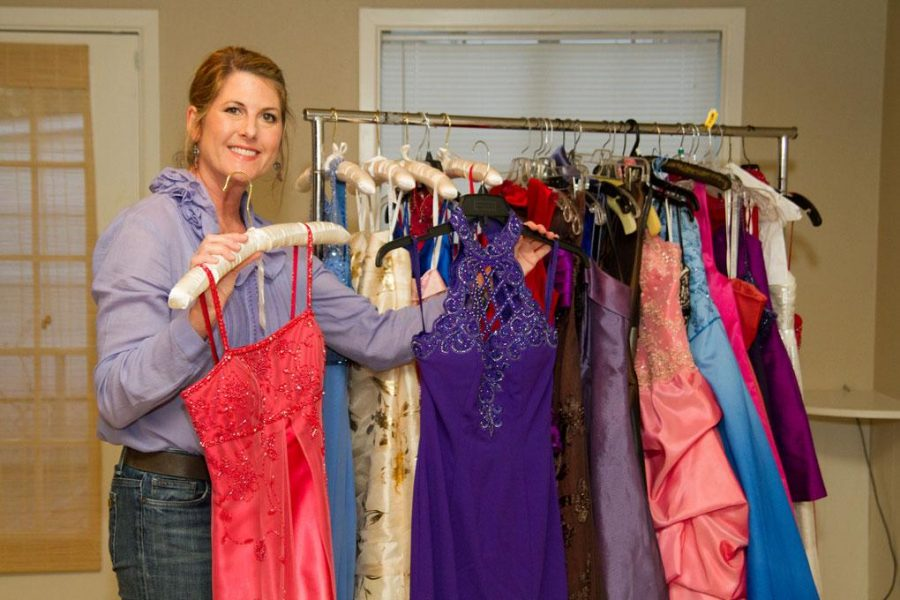 Prom mom Julie Tidwell shows dresses to the camera as she prepares for the prom boutique.