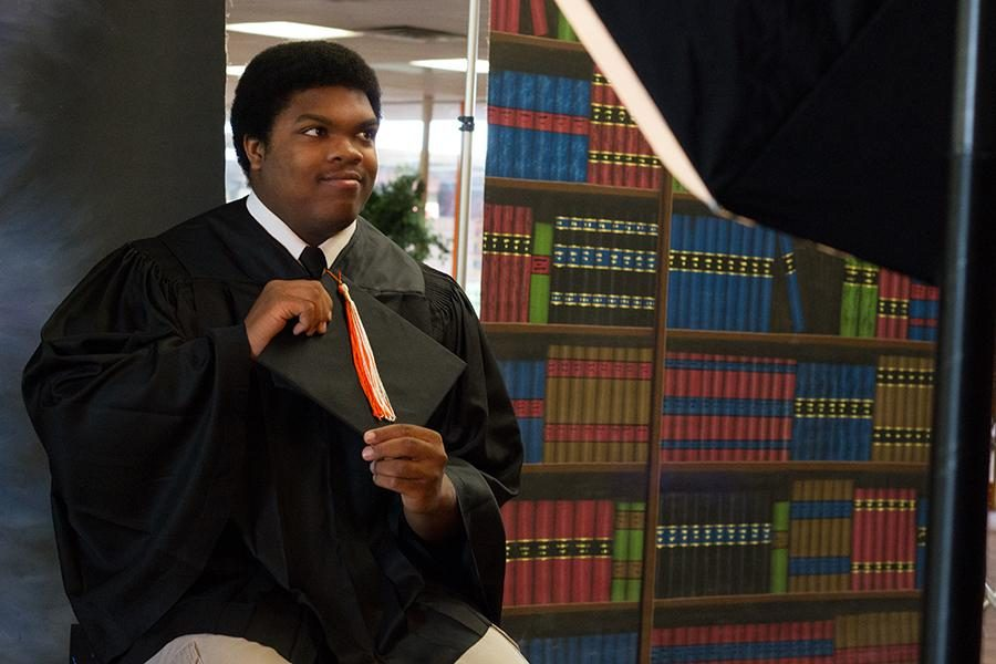 Senior+Justin+Lewis+gets+his+cap+and+gown+photo+taken+during+the+summer.+Retakes+will+be+Sept.+9.