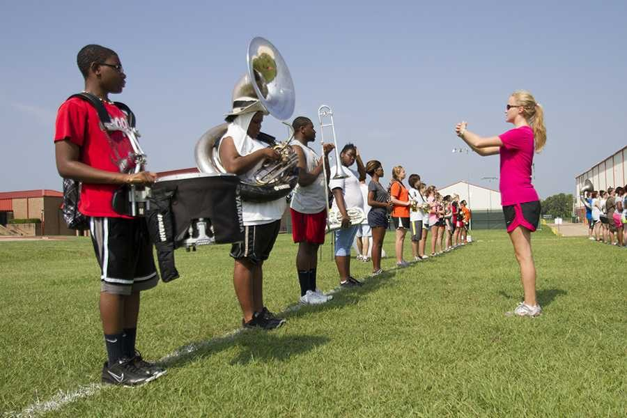 Senior drum major Madison Norton works with band members during summer practice.