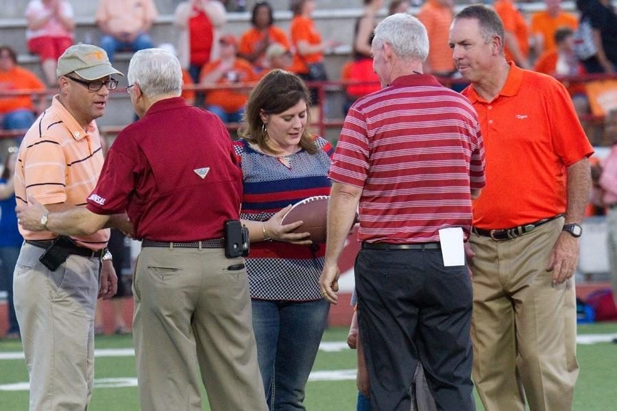 Former Texas High teacher Stephanie Sprague received a commemorative game ball in honor of her late husband, Officer William Sprague, during the annual Texas vs. Arkansas game.
