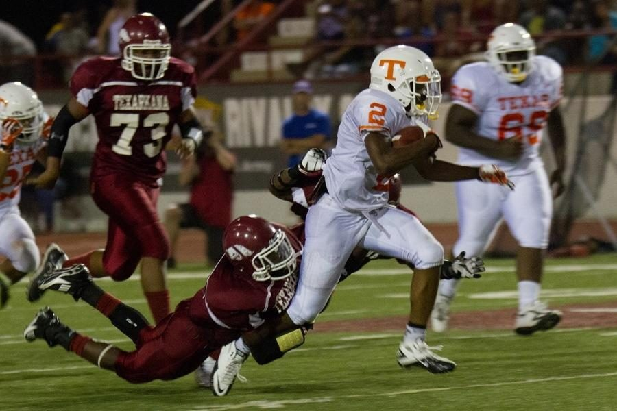 Trying to bring him down, Arkansas High defenders grasp at senior Treveon Walker's legs.