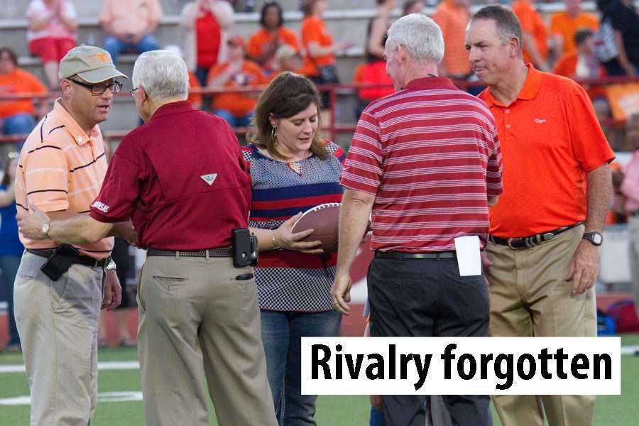 Former Texas High teacher Stephanie Sprague receives a commemorative game ball in honor of her late husband, Officer William Sprague, during the annual Texas High versus Arkansas High football game Friday.