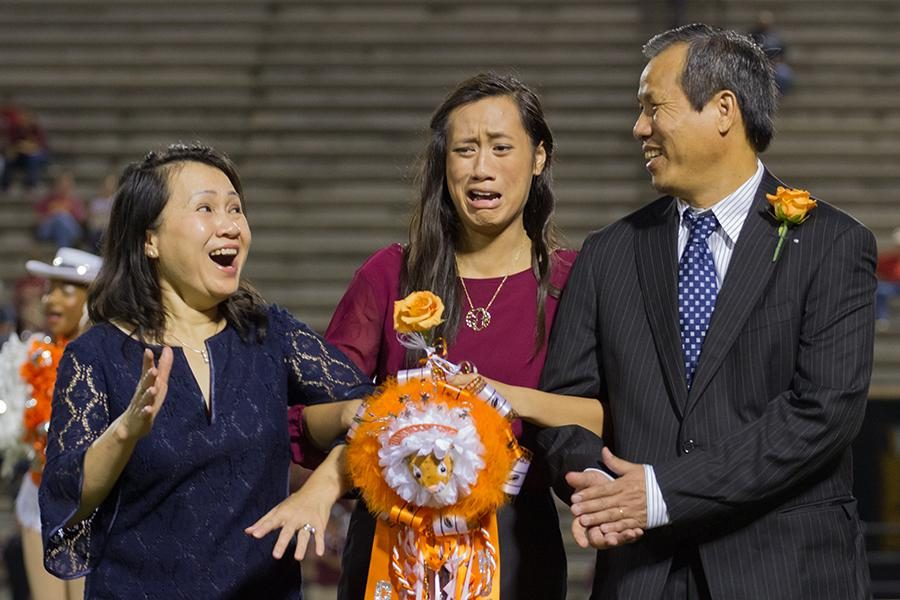 Senior Chau Dong, along with her parents, reacts to being named homecoming queen Friday at Grim Stadium.