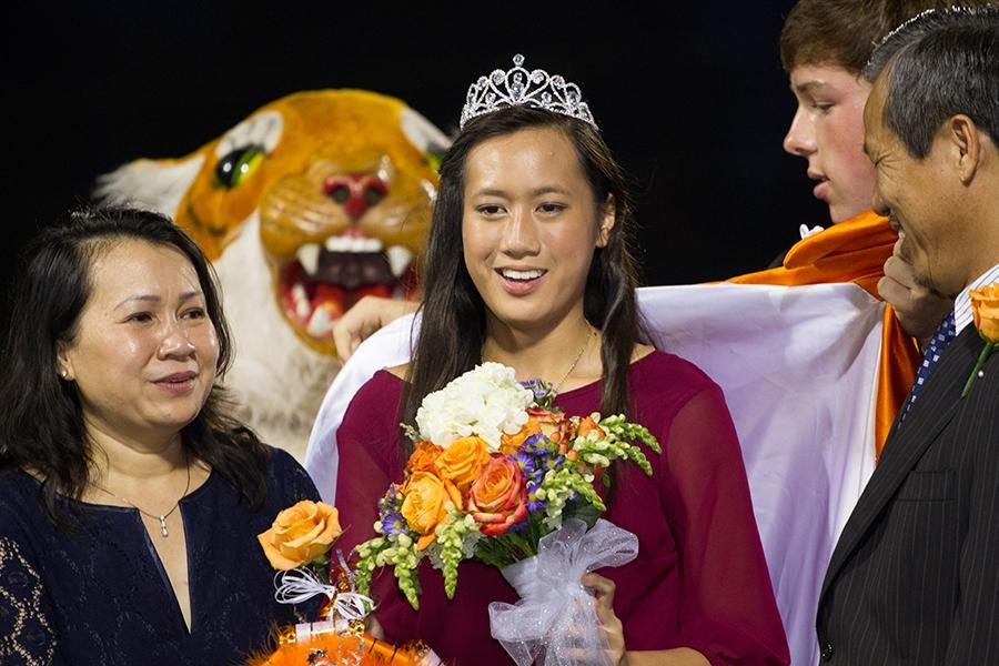 Surprised to be named homecoming queen, senior Chau Dong stands on the field with her parents Friday at Grim Stadium.