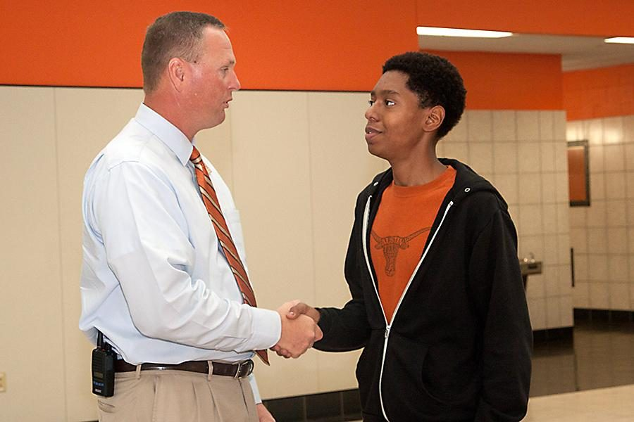 National Merit Semifinalists Courtandt Bursey-Reece receives a congratulatory handshake from principal Brad Bailey.