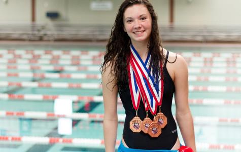 Freshman Alex jones standing with her Junior Olympic medals.