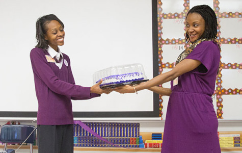 Britny Ray, along with other members of the English department, congratulate Monica Washington and present her with a cake.