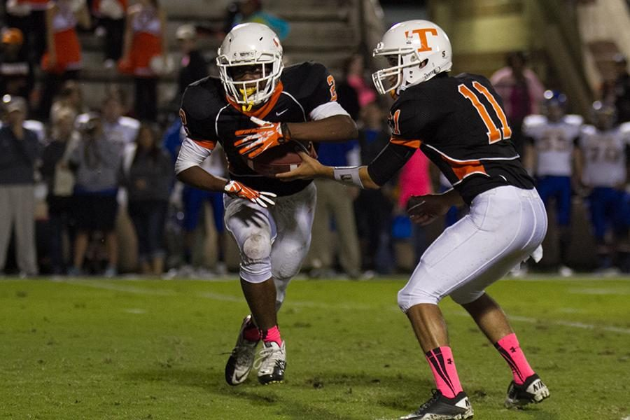 Senior quarterback Dakota Hunter hands the ball off to senior running back Treveon Walker.