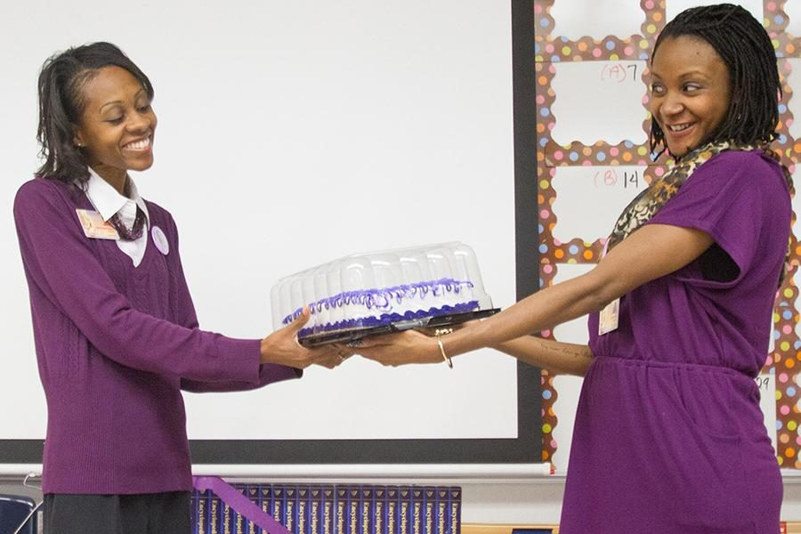 In addition to wearing purple in honor of Monica Washington winning state teacher of the year, fellow English teacher Britny Crowell gives Washington a cake.