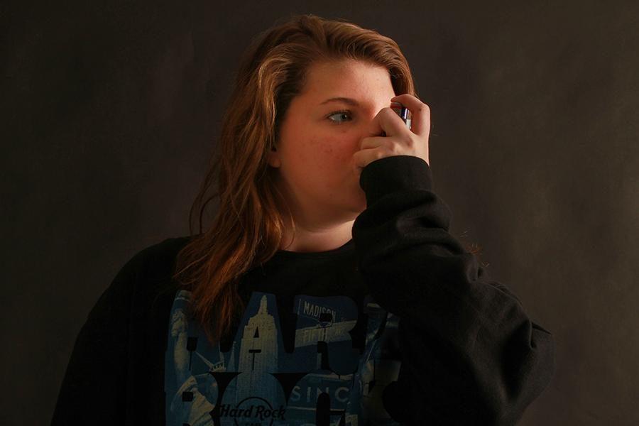 Walker takes a puff of her inhaler.