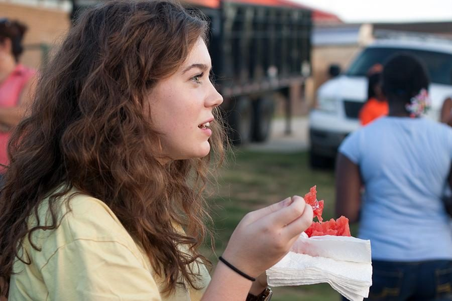 Sophomore Grace Hickey dives into a slice of watermelon during the annual Watermelon Supper Aug. 23