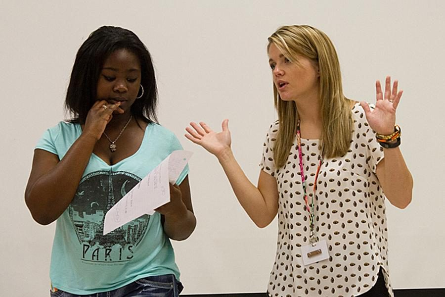 On the right, new teacher Lindsey Thompson gives direction to class
