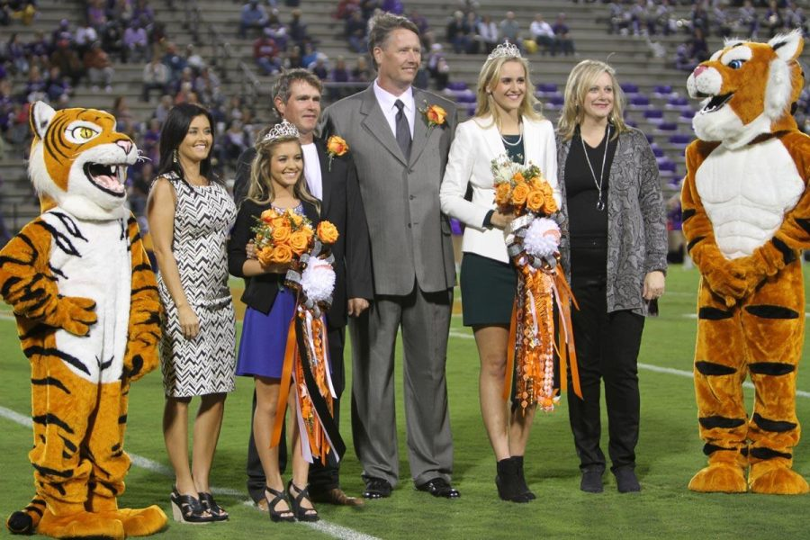 Seniors Autumn Jester and Chandler Thomas stand with their parents on the field after being crowned homecoming queens in a tie.