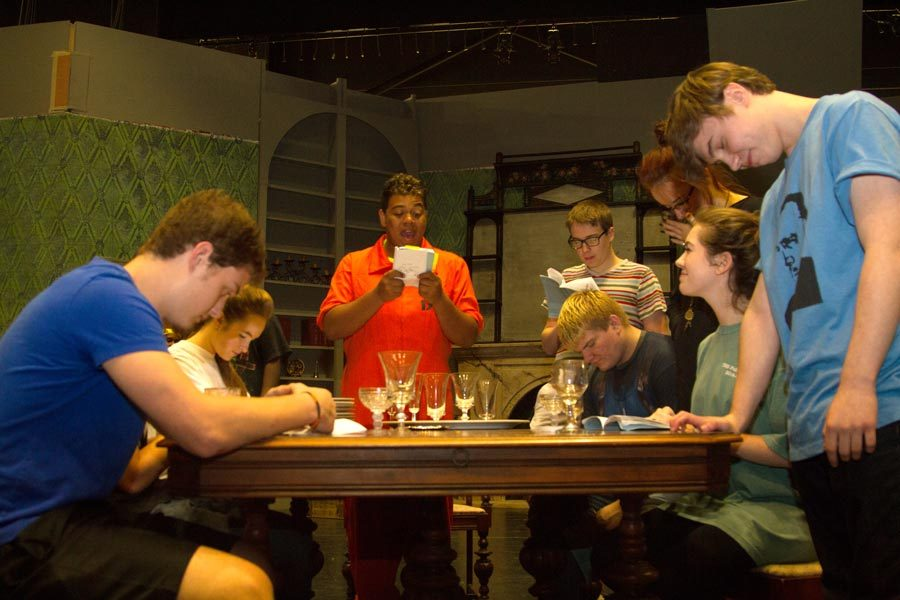 Cast members practice the dinner scene of the play