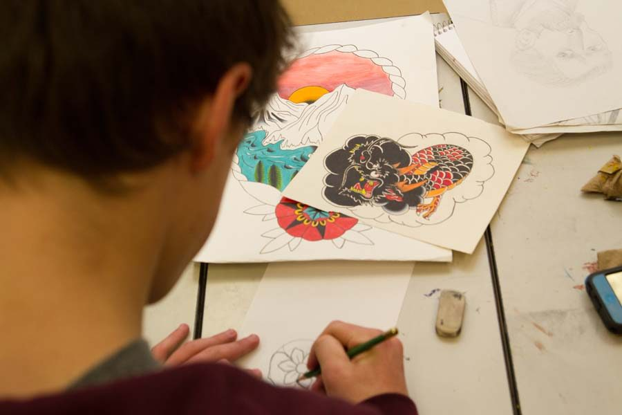 Artist Connor Anderson focuses on a few sketches in class