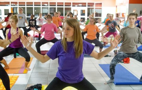 Senior Megan Haselow hits crouching asana with fellow Rosebuds' members in Cafeteria