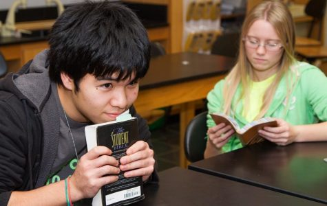 Juniors Hoshiki Reyes rest his chin on a student Bible while junior August Welcher looks for scripture during a discussion at a Fellowship of Christian Students meeting.