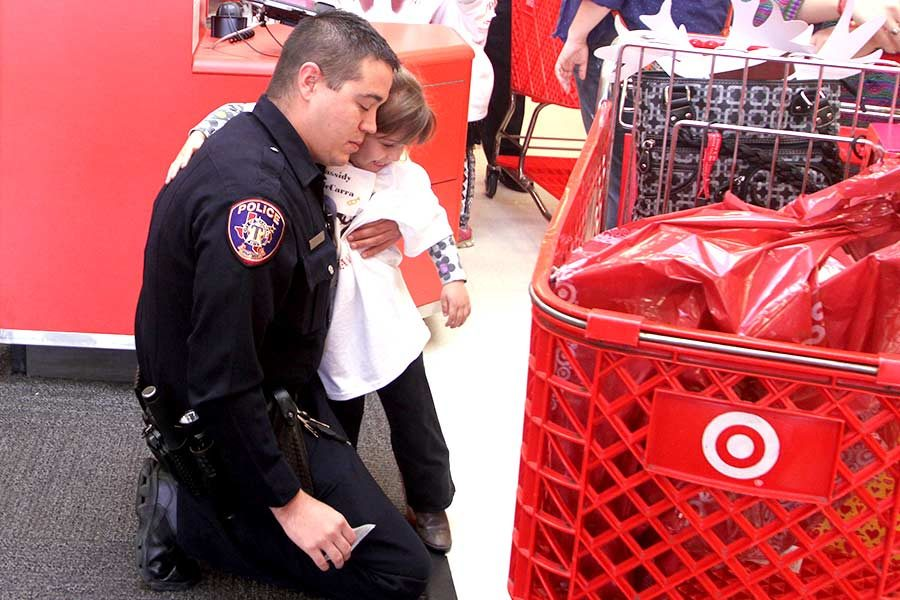 Officer hugs child participant in the event Heroes & Helpers goodbye as they finish a morning of shopping