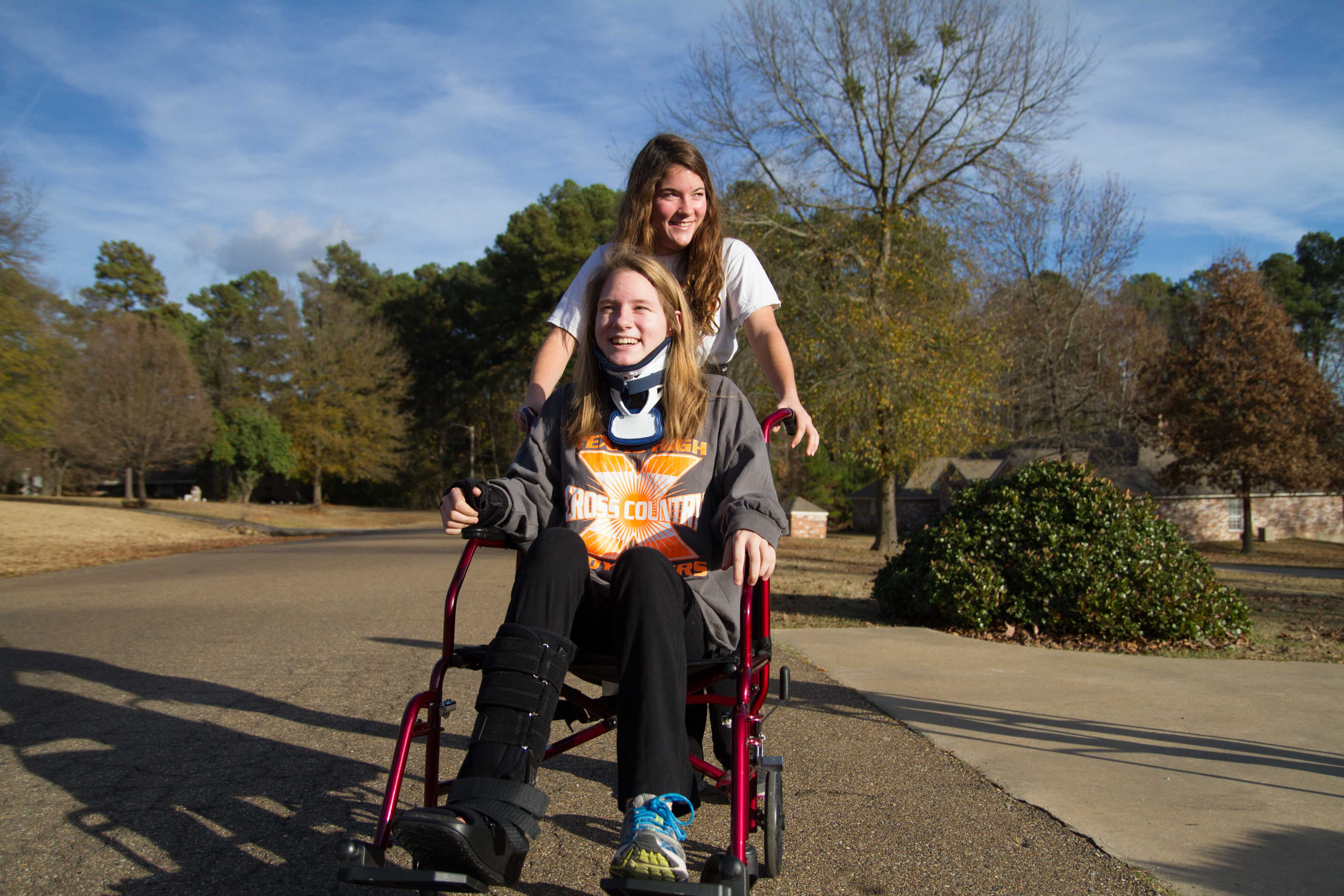Paige Gibbert helps sister Lauren Gibbert by pushing her in a wheelchair