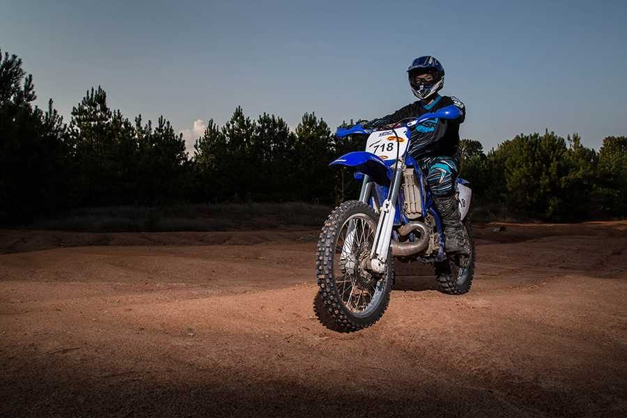 Darren Mooney poses with his dirt bike on a course he uses to practice for competition