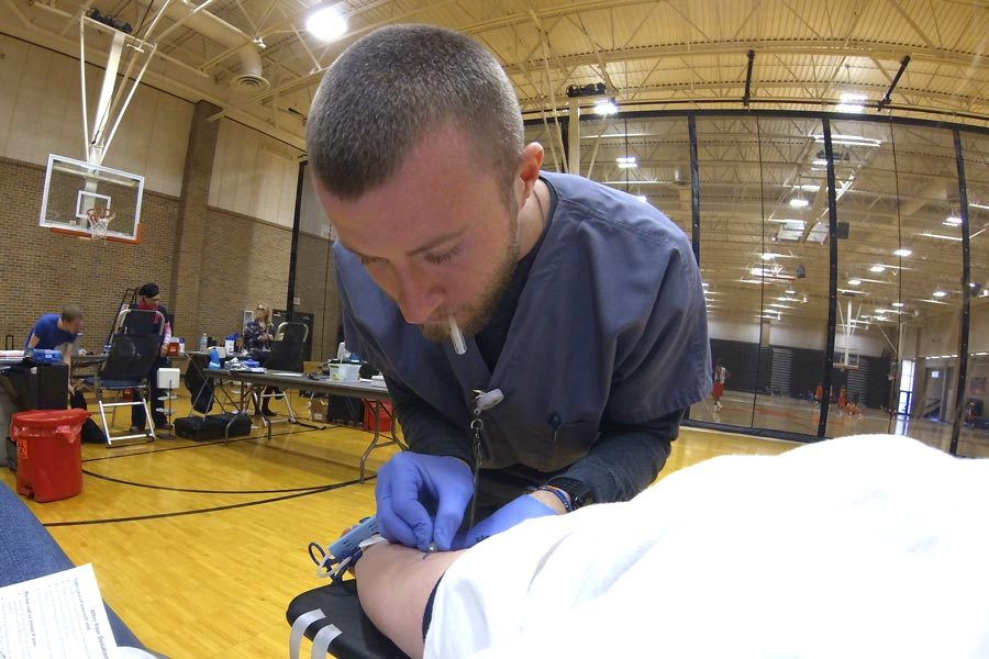 Senior Katie Johnston watches the United Blood Services technician guid the needle into her arm during the Blood Drive held in the Texas High School Tiger Center.