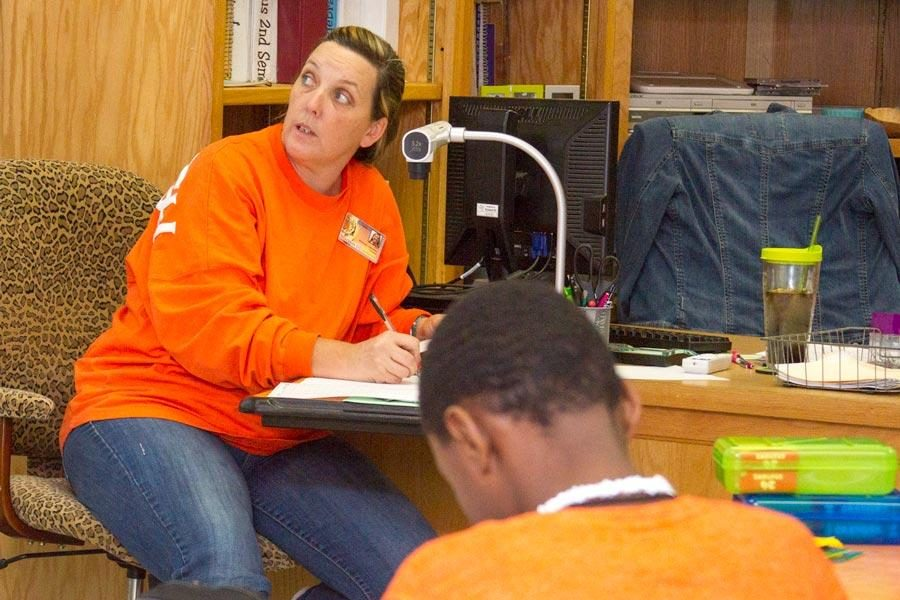 Rhonda Johnson peers works through math problems with her students at Texas High School.