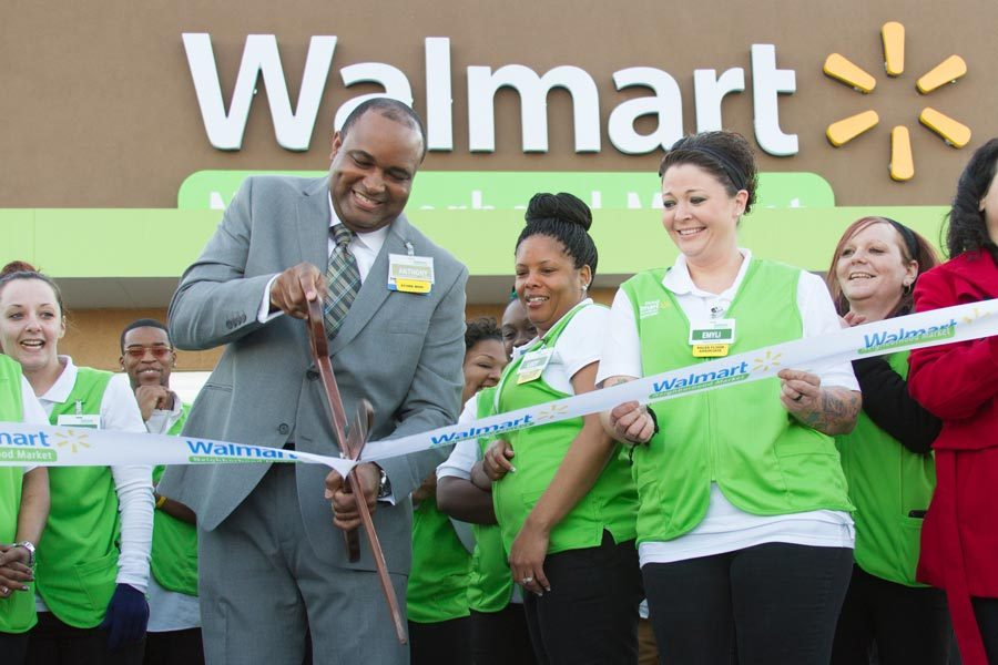 Store manager Anthony Porchia cuts ribbon with employees signifying the opening of the new Neighborhood Market Walmart. The new store is being affectionately called the