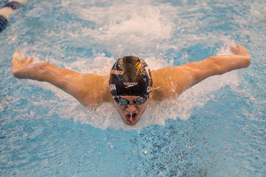 Junior Luke Calhoun gasps and fights water as he competes in relay at District meet.