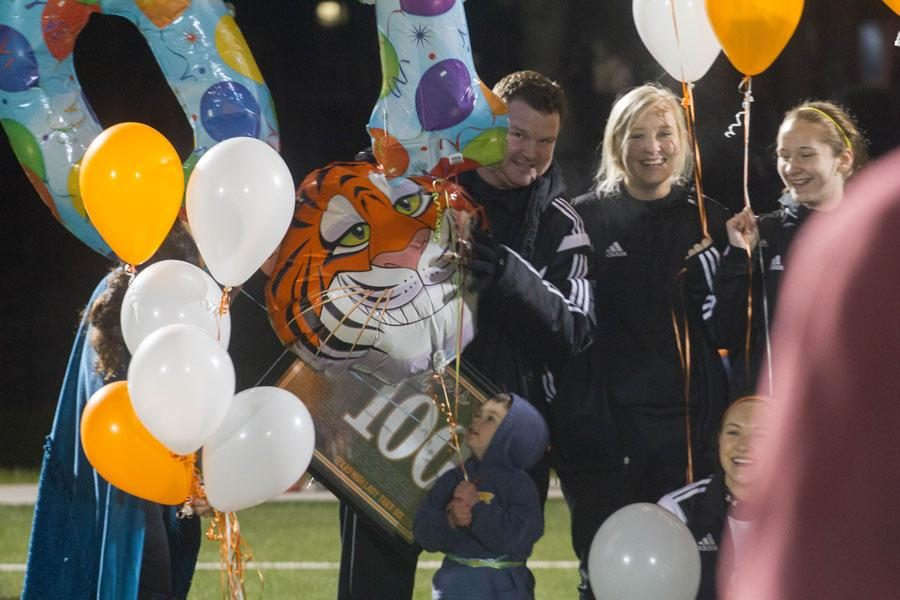 Coach Dustin Holly peaks around balloons given to him to celebrate his 100th coaching victory at Texas High School.