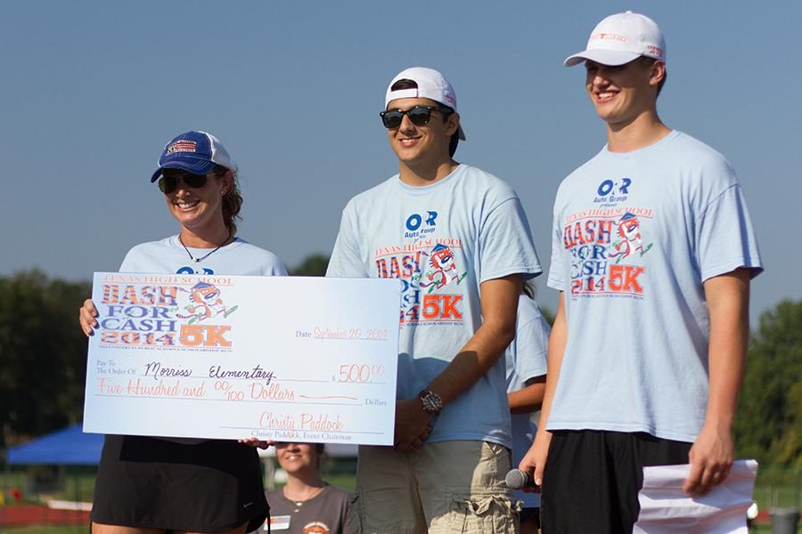 Seniors Gage Martin and Nick Richter donate money to the elementary school.