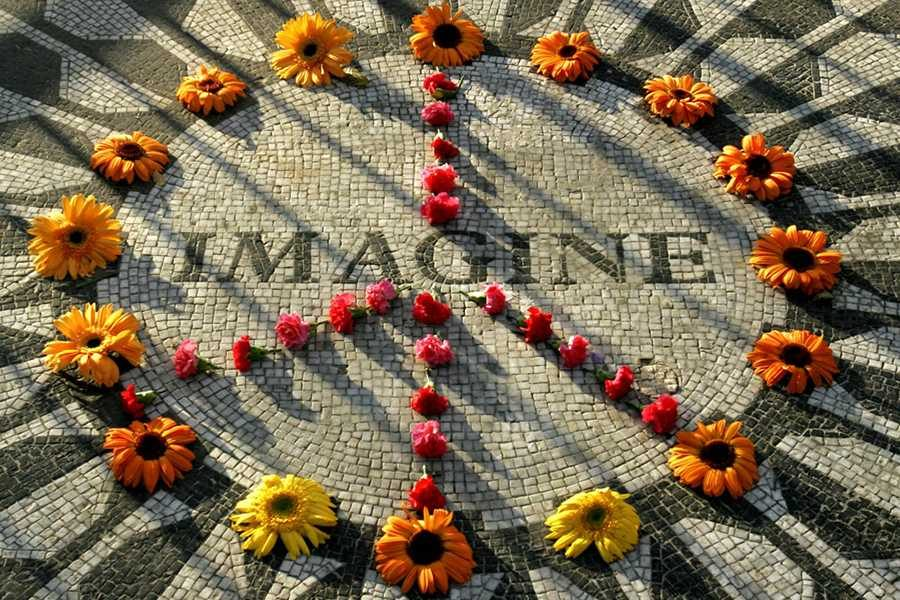 A makeshift peace sign of flowers lies on top John Lennon's