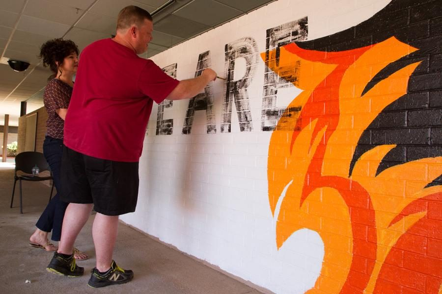 Art teachers Rebecca Hill and Tyson Feemster fill in the words of the mural. It reads