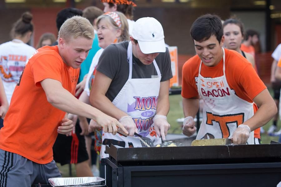 Seniors Nick Kelley, Braden Sellers and J.T. Morgan scramble eggs and fry bacon to feed the student body during the 2015 Bacon Fry at Texas High School.