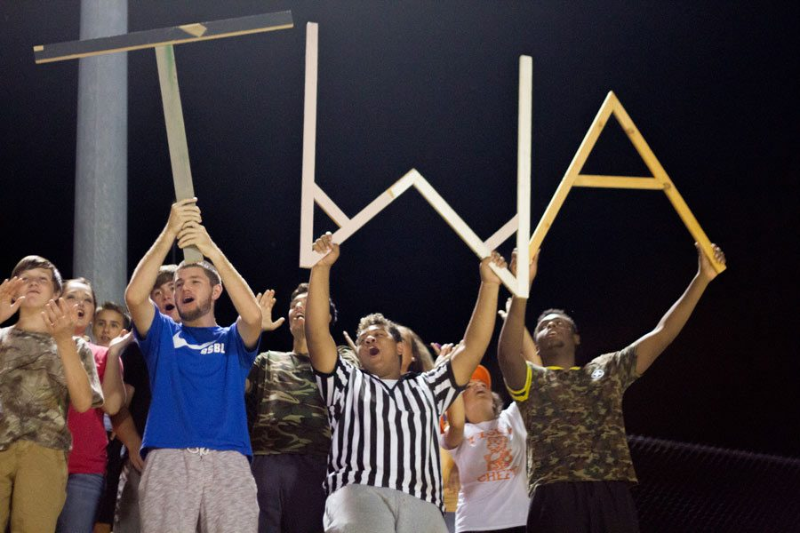 Seniors Colton Russell, Colby Gillespie and Jacoryon Larry hold T.W.A at the JV Football game against Arkansas High.