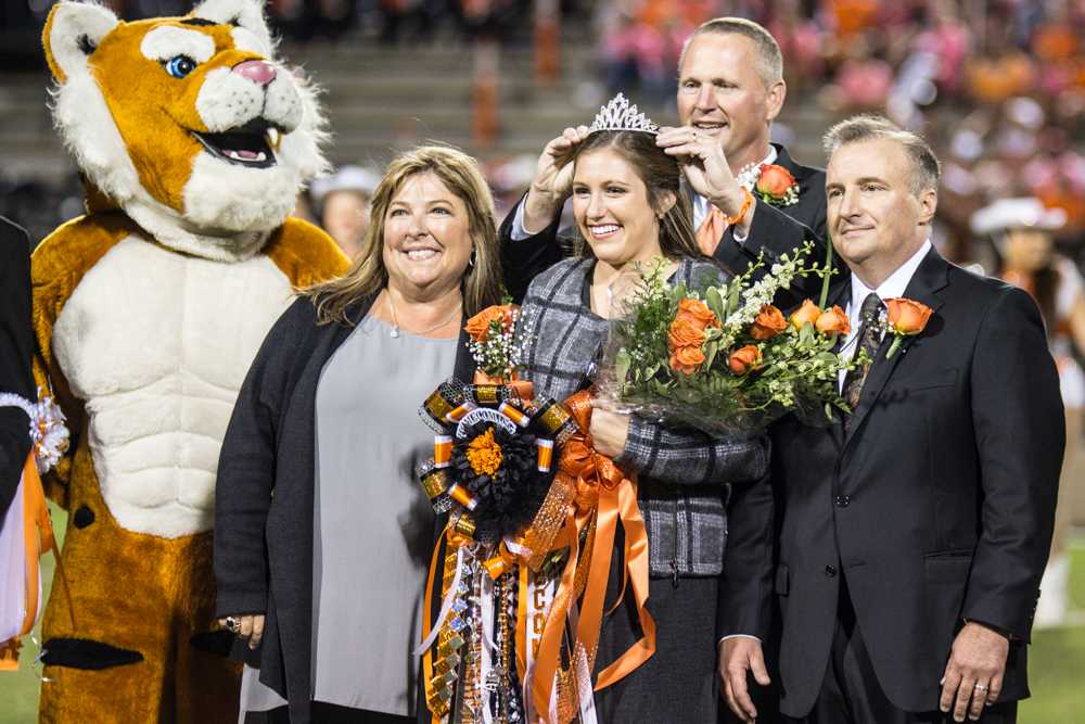 Principal Brad Bailey crowns Senior Anna Catherine Boudreaux as parents Tracy and David Boudreaux stand alongside.