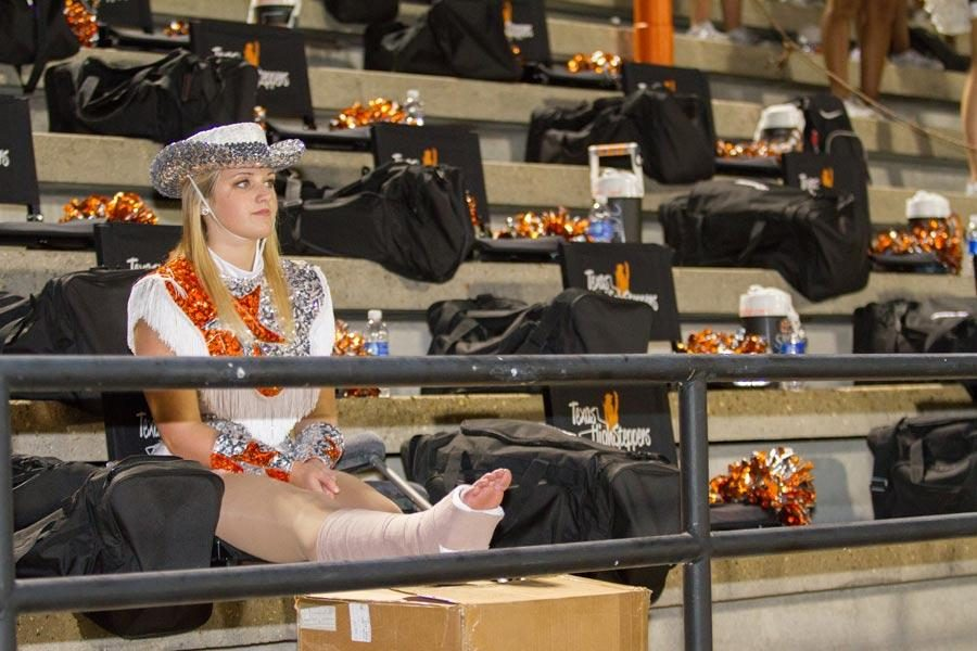 Senior Brooke Rayburn watches her fellow Highsteppers perform at a football game. Rayburn will be unable to dance until December.