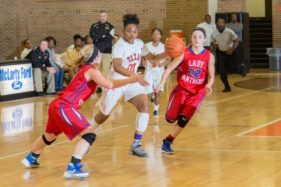 Freshman Antonia Porter attempts to drive past the Alba-Golden defenders. The Lady Tigers were defeated 75-65 by the Alba-Golden Lady Panthers.