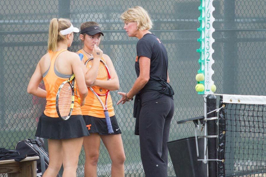 Coach Anne Tarwater consults with senior Aubree Cramer and junior Ali Richter during their doubles match.