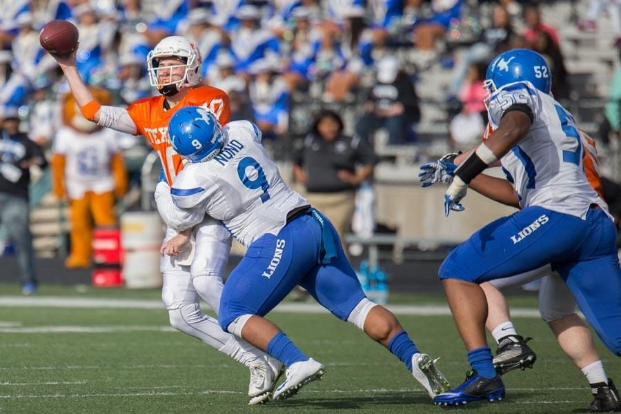 Texas High quarterback Cade Pearson is pressured by John Tyler defensive lineman Pierre Leonard. Texas High was defeated 48-21 ending the Tiger's 2015 football season  with a record of 8-3.