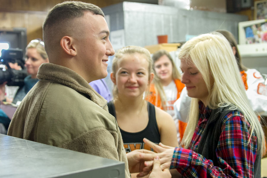 Airman Sawyer Spaulding holds his sister Piper's hand while his youngest sister Hartley beams with excitement after Spaulding surprised his sisters in his mother's classroom Thursday.