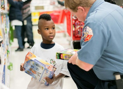 A Texas side firefighter helps one of the children selected to be part of Shop With A Cop and Firefighter at Target. Children selected for this event are given $100 to spend on whatever they want for Christmas.