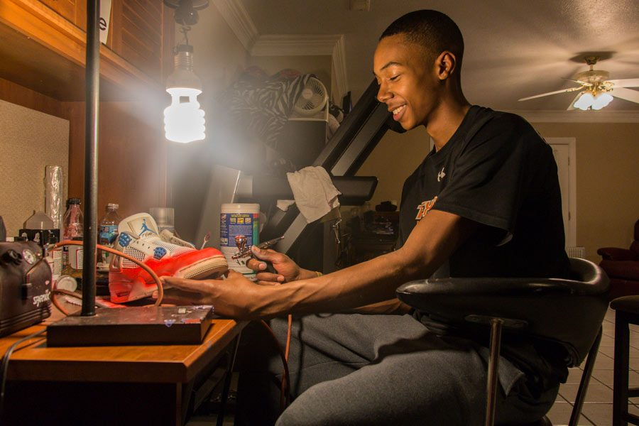 """Senior RJ Reid custom paints a  shoe. """"There's a lot that goes into [making customs],"""" Reid said. """"Most people think that it's just getting a pair of shoes and painting over the top of it, which it's not at all. When I'm finished with the paint, I still have to put a cover on it so the paint won't just scrape off because you wear them."""""""