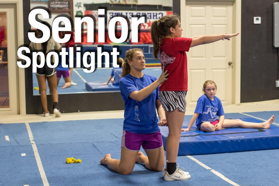 Senior Shaleigh Chandler spots one of her students as she prepares to do a back handspring. Chandler plans to become a physical therapist.