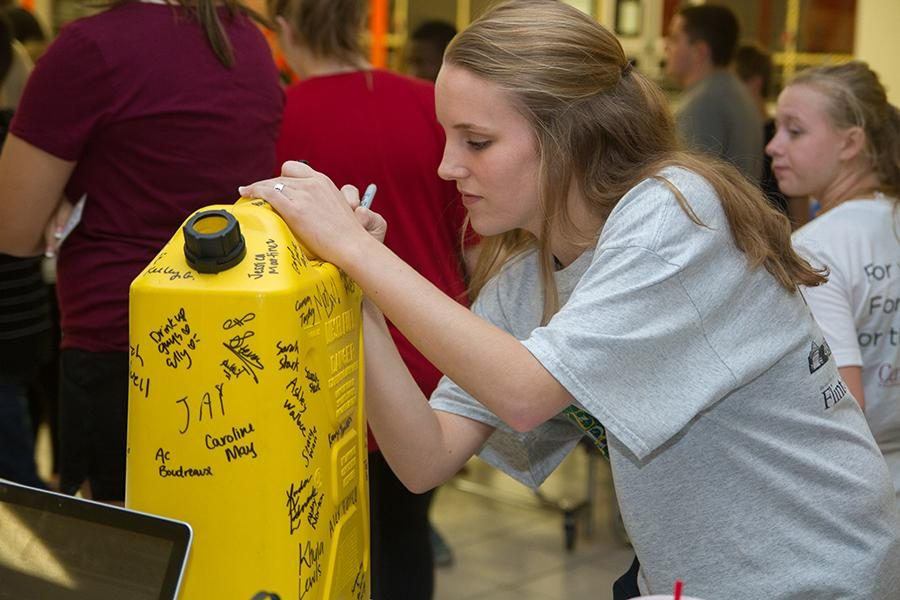 Senior Anna Graves signs thirst project jug in support of her pledge.