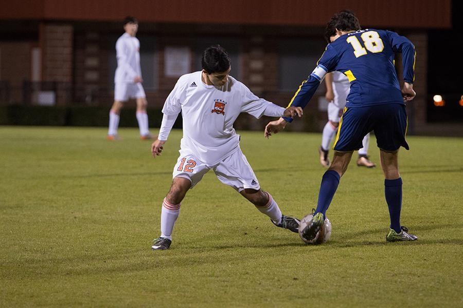 Junior Alejandro Hernandez dribbles the ball past a defender.