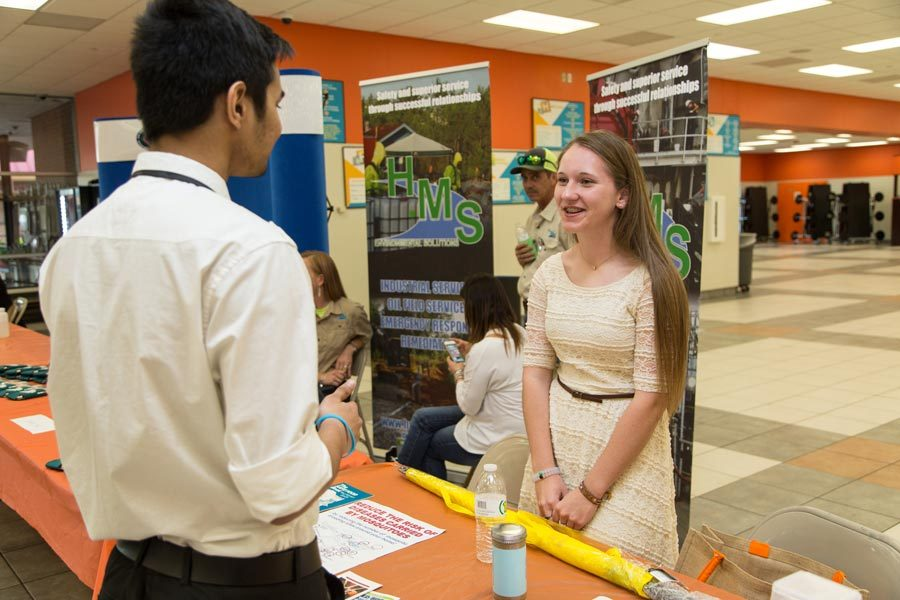Junior Rachael Shewmaker presents her business to a student at the Environmental Expo.