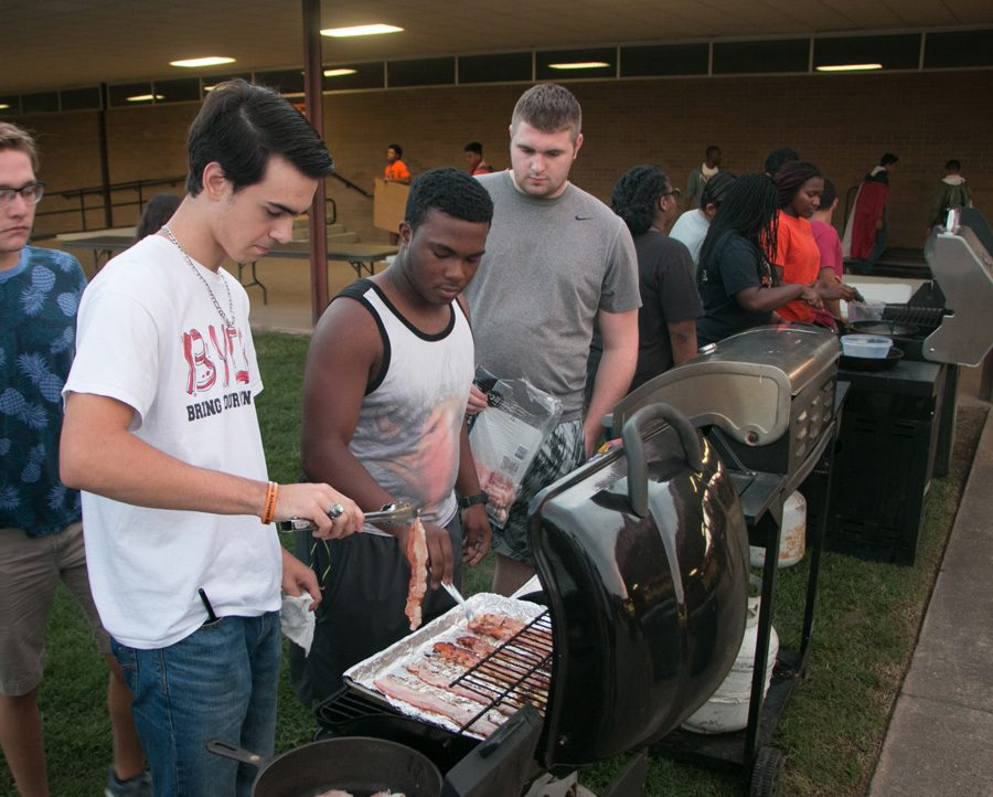 Seniors Grant Owens, Jordan Thomas and Dylan Raley cook bacon on a grill during the bacon fry. The morning before the Texas vs. Arkansas game seniors gather to prepare breakfast for the student body.