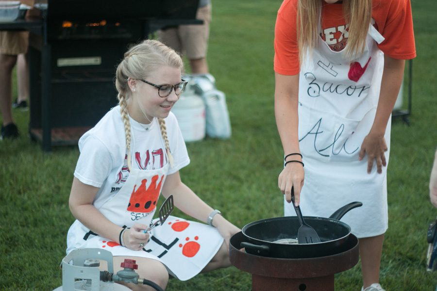 Senior Lauren Maynard cooks bacon on a small pan during the annual bacon fry. The morning before the Texas vs. Arkansas game seniors gather to prepare breakfast for the student body.